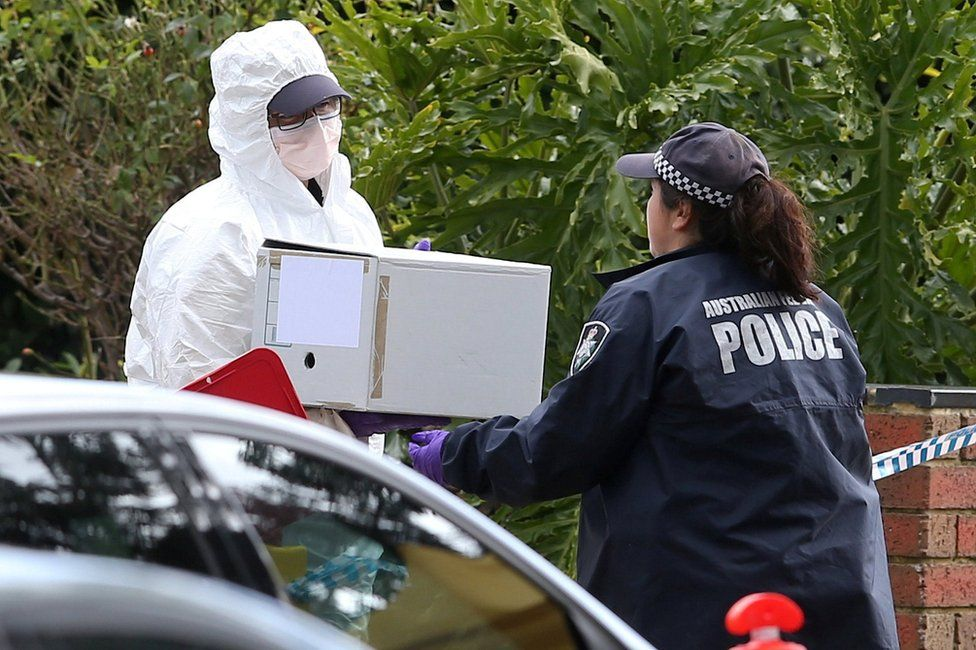 Investigators carry a box of evidence from the house gunman Yacqub Khayre is believed have shared with his mother