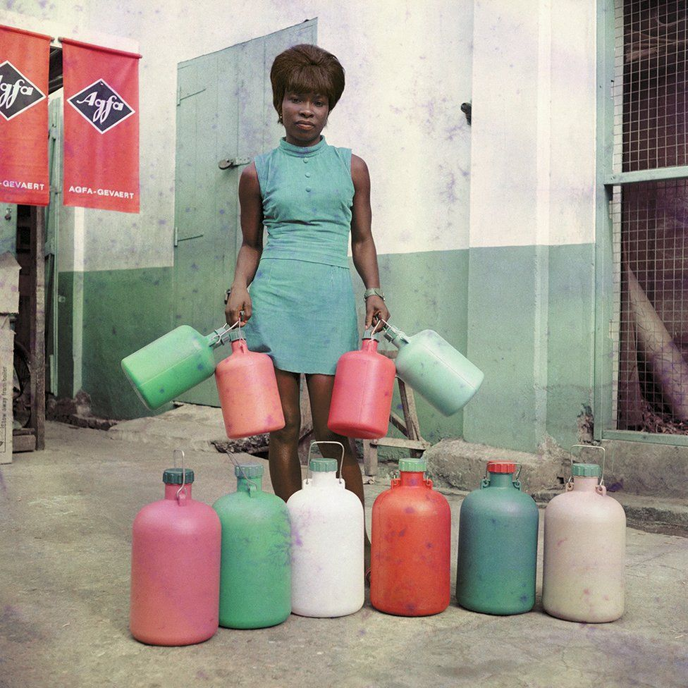 Woman standing outside holding containers