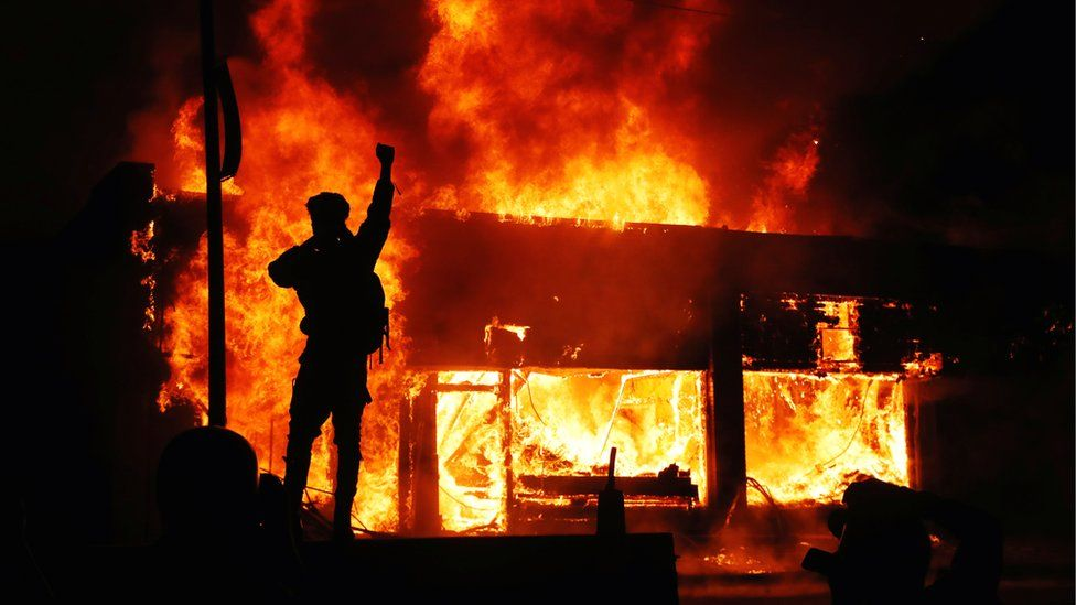 A protester gestures as buildings burn during continued demonstrations against the death in Minneapolis police custody of African-American man George Floyd, Minnesota