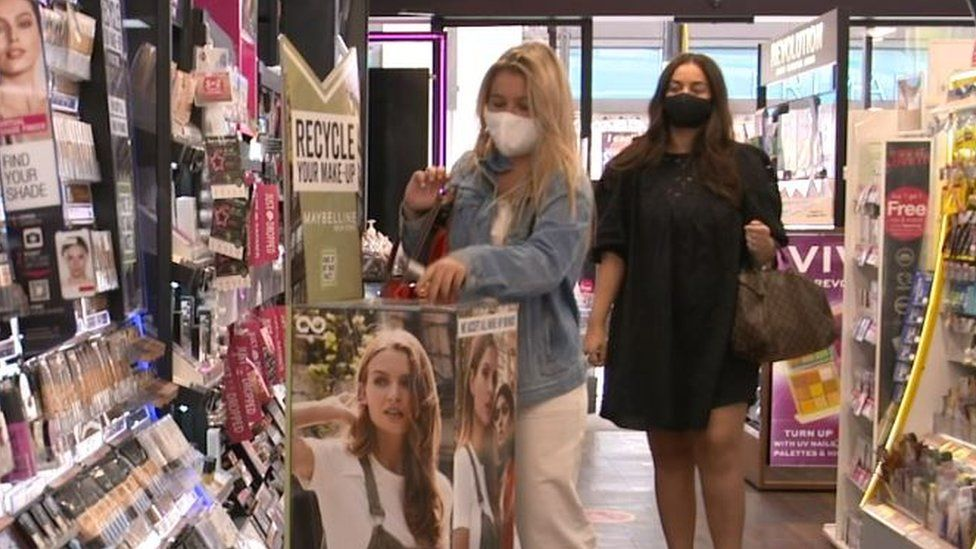 Customers using the recycling point at a Superdrug store