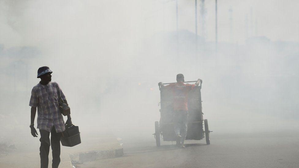 A local cobbler walk past smoke emitting from a dump
