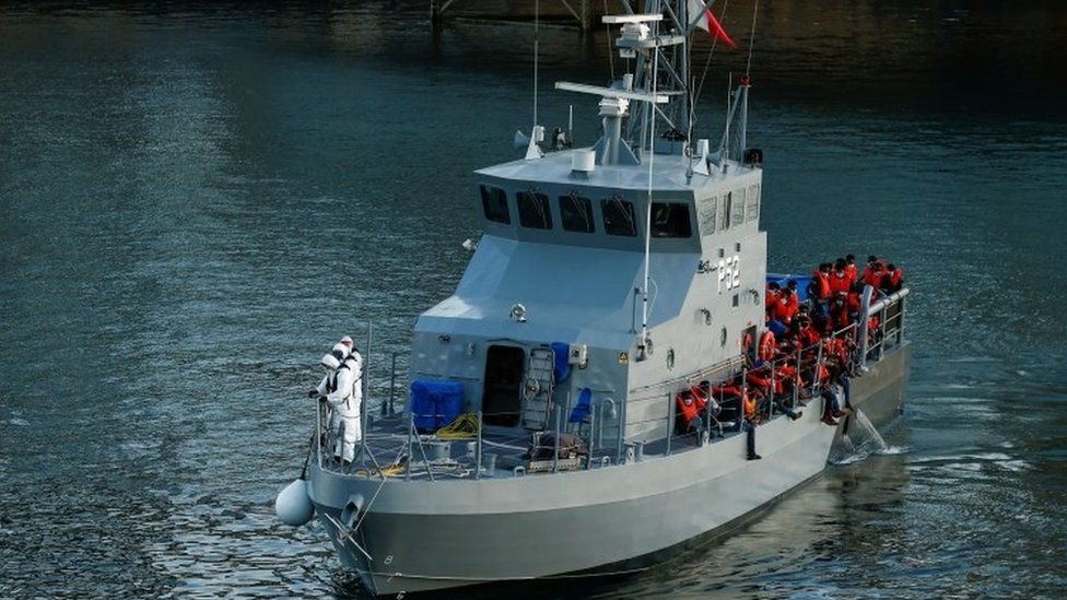 Rescued migrants are seen on an Armed Forces of Malta vessel after arriving in Valletta's Grand Harbour