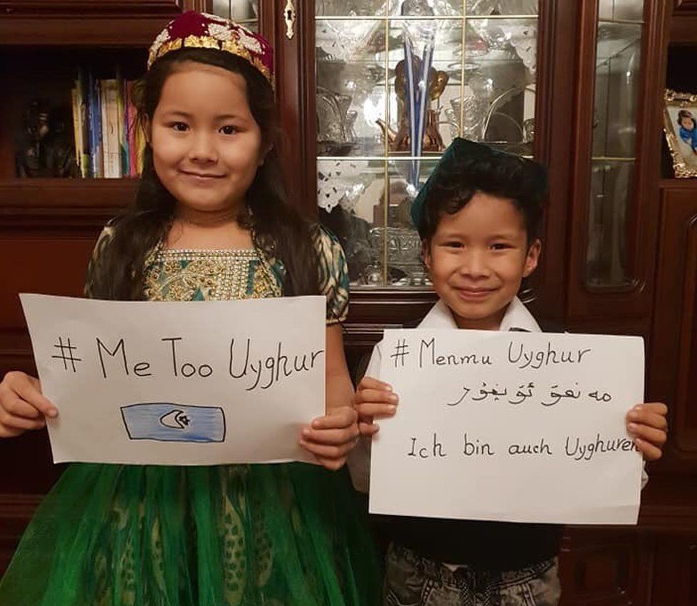 Two children holding up #MeTooUyghur posters