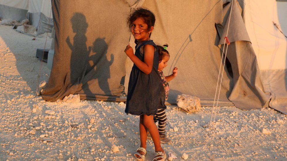A displaced Syrian girl stands next to a tent provided by a Turkish humanitarian organisation at a camp for displaced people in northern Idlib province, 29 August 2018