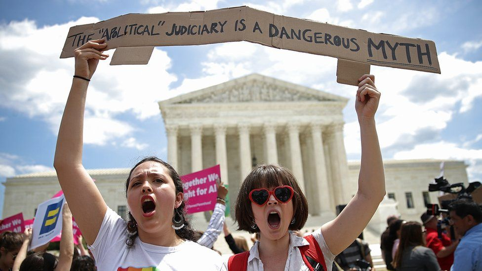 Protesters gather outside the US Supreme Court following a court issued immigration ruling 26 June