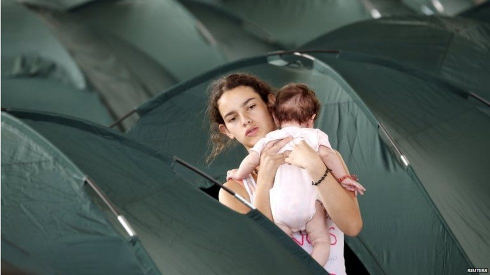 A deported teenager holds a baby amidst tents at a temporary shelter in Villa del Rosario in Colombia on 29 August, 2015.