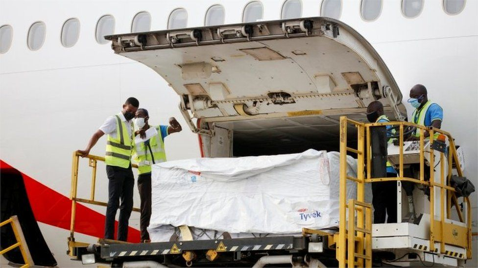 Workers offload boxes of Oxford-AstraZeneca vaccines as the country receives its first batch under Covax scheme, in Accra