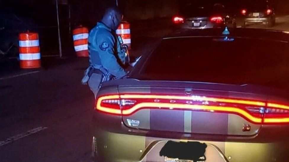 An Atlanta Police officer stands next to a car equipped for street racing, in a police picture posted on Facebook, on 21 December 2020