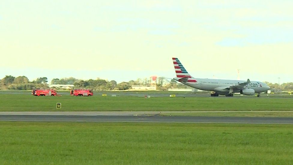 An American Airlines plane is followed by fire crews as it taxis across the runway at Dublin airport