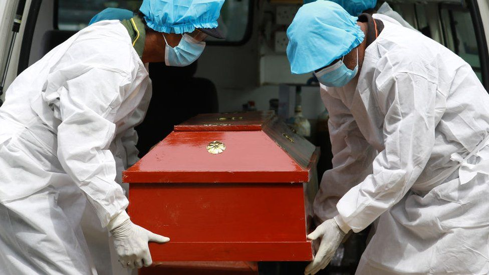 Sri Lankan municipal cemetery workers dressed protective suits carry a coffin of a Covid-19 virus victim for cremation at Colombo, Sri Lanka. 21 December 2020.