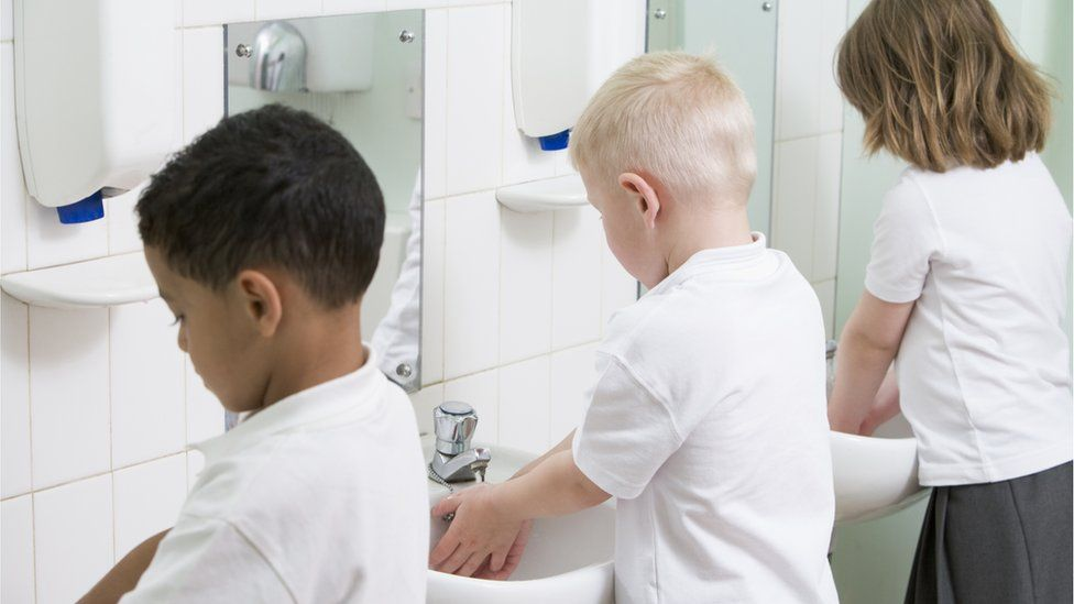 Young children washing their hands at school