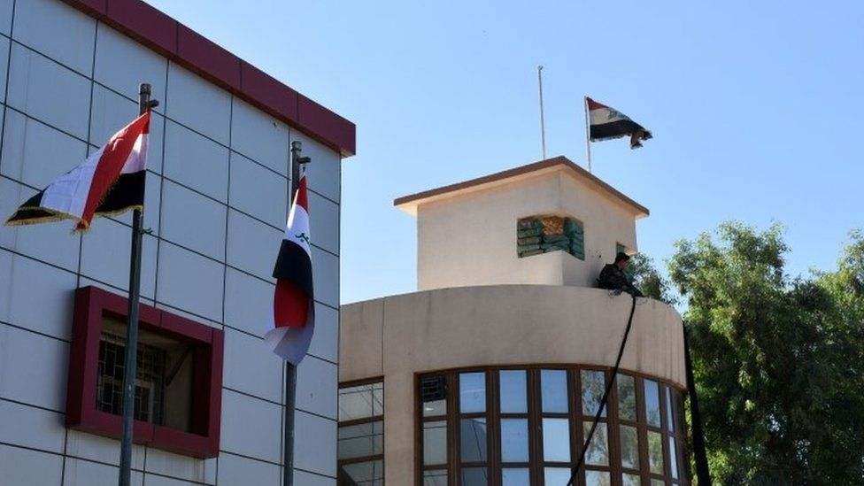 The Iraqi national flag swaying to the wind above the Kirkuk Governorate building in the multi-ethnic northern Iraqi city (17 October 2017)