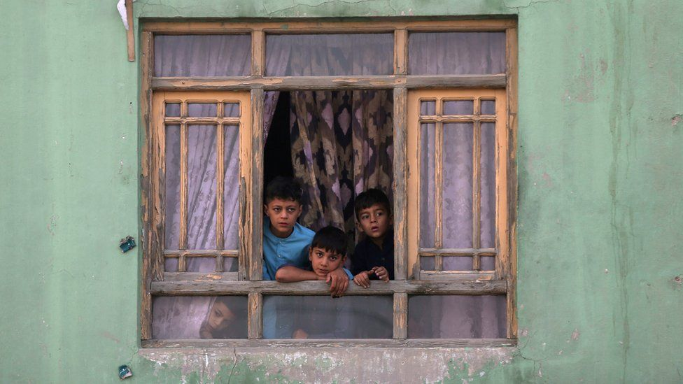 Afghan children looking out of a window
