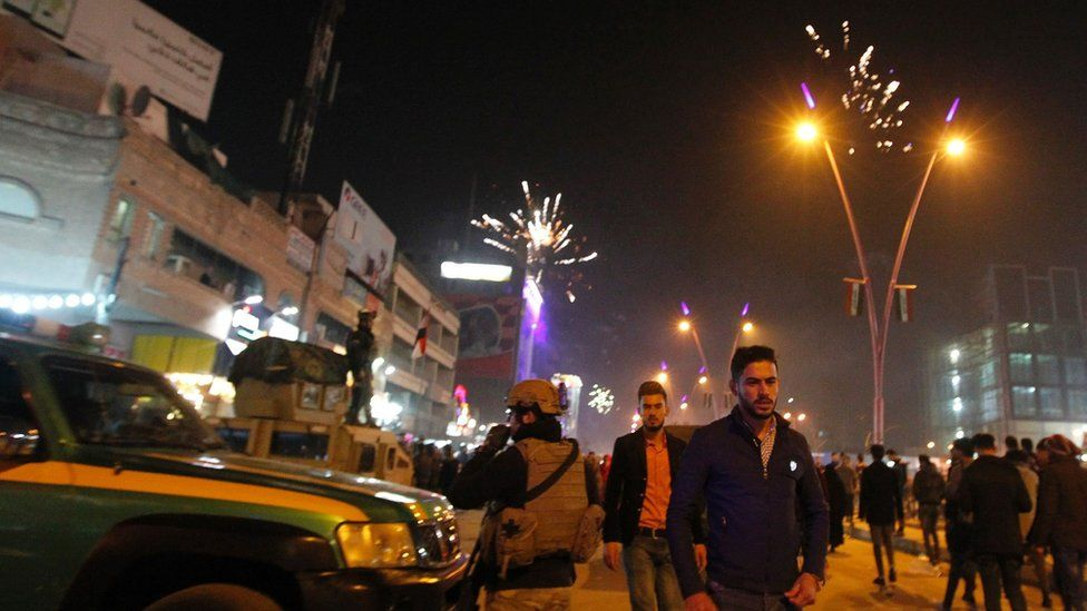 Iraqi walk past security forces as they gather at the al-Mansour square during Christmas and New Years eve celebrations in the capital Baghdad