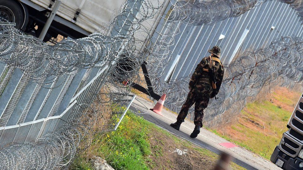 A Hungarian soldier patrols at the Hungarian border fence at the Tompa border station transit zone on 6 April 2017