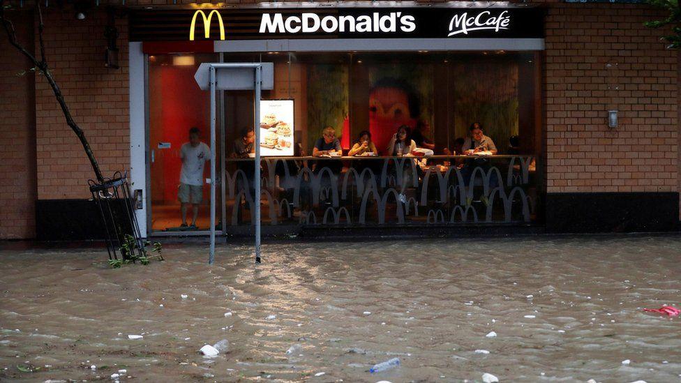 香港杏花邨一家麦当劳餐厅顾客观看店外被淹没的马路(23/8/2017)