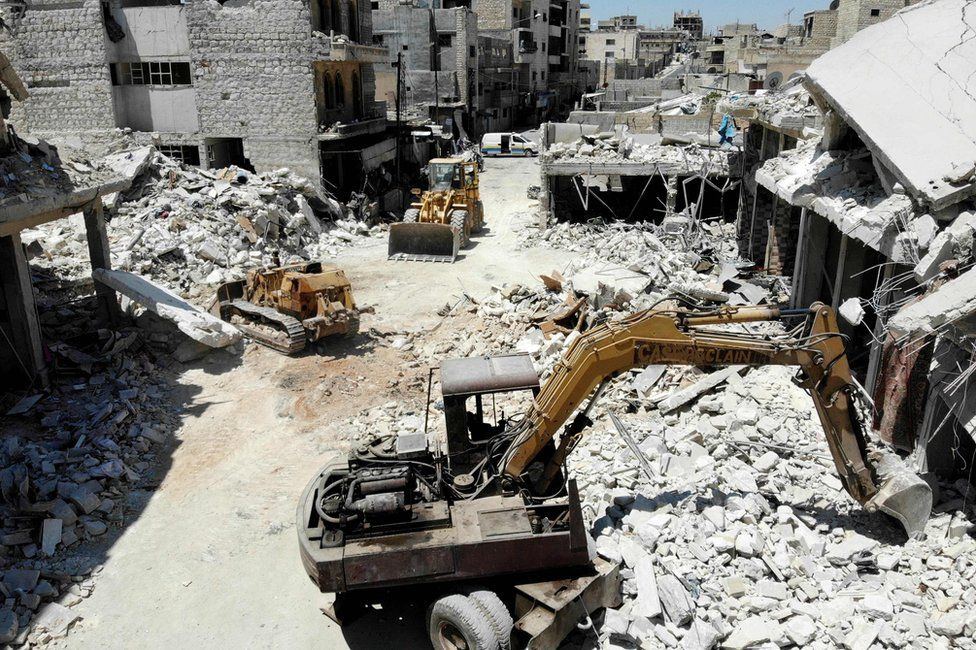 Excavators and bulldozers are used to search for victims after an air strike on a market place in the opposition-held town of Maarat al-Numan, Syria (22 July 2019)