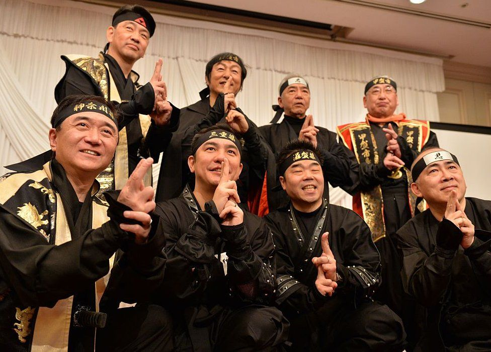 Governors and mayors from Mie, Shiga, Kanagawa prefecture and former tourism agency chief Hiroshi Mizohata (first row, R) pose in ninja costumes for photos as they hold a press conference in Tokyo on 8 March 2015.