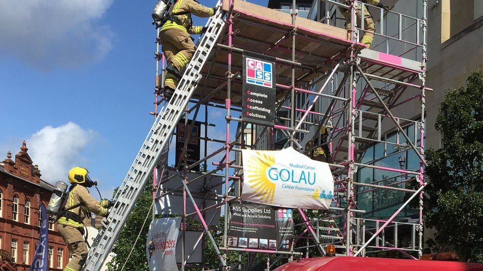 Picture of the firefighters climbing the ladder