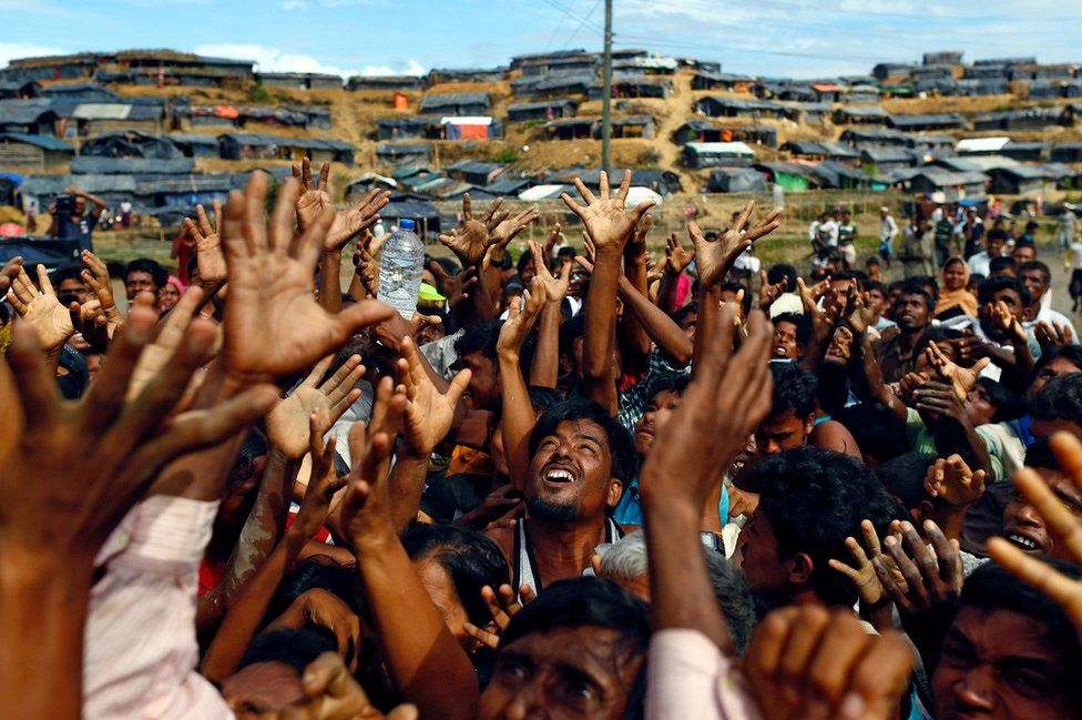 Rohingya people stretch their hands to receive aid distributed by local organisations at Balukhali makeshift refugee camp in Cox's Bazar, Bangladesh on 14 September 2017.