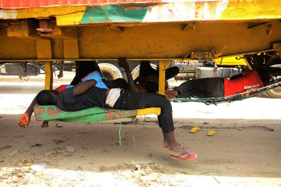 Truck drivers taking a nap, using their trucks as shade.