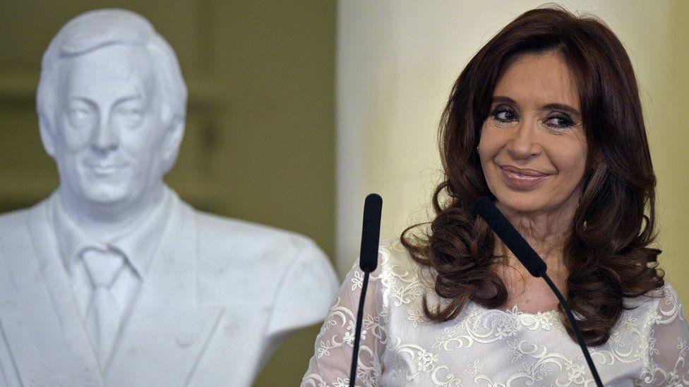 Cristina Fernandez de Kirchner next to a bust of her late husband Nestor