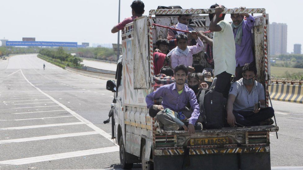 Migrant workers headed back to their towns and villages hitch a ride, on day 5 of the nationwide lockdown imposed by PM Narendra Modi to check the spread of coronavirus, at Yamuna expressway zero point, on March 29, 2020 in Noida, India
