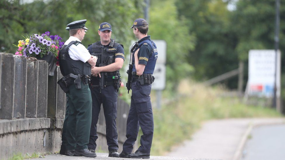 PSNI and the Garda officers stand exactly on the border in Belleek, County Fermanagh, ahead of Theresa May's visit