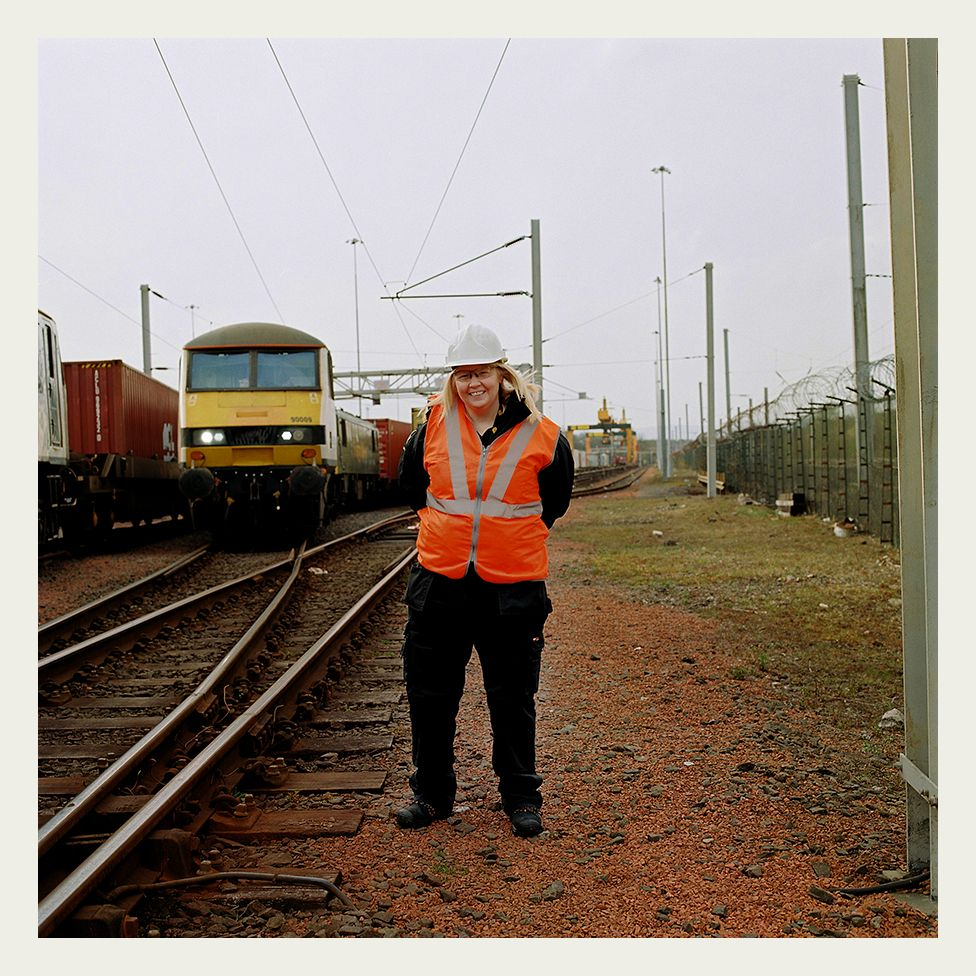 Heather Waugh, stands in front a Class 90 locomotive, at the start of her shift