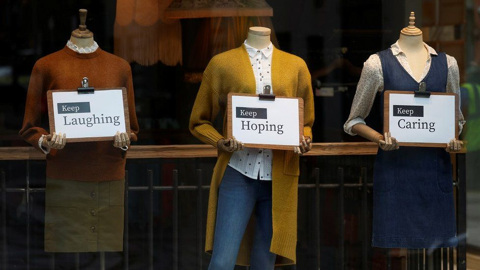 Shop mannequins hold motivational signs in the window of a closed Manchester clothing store, in February