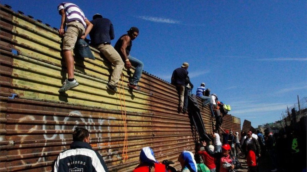 Migrants climb the border fence between Mexico and the United States