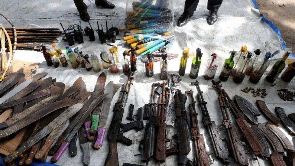 Rifles, machetes and petrol bombs on display.