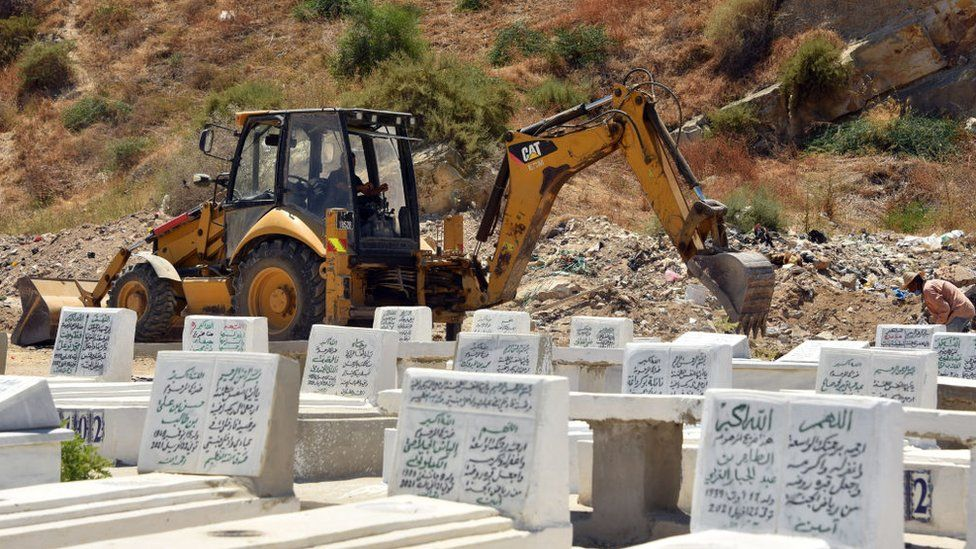 A digger tears the ground up for graves in Tunisia, July 2021