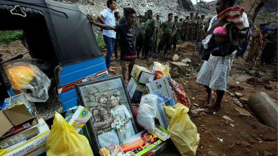 Occupants of a buried house with their possessions - a three-wheeler, their large wedding photograph and some salvaged items at the site of a collapsed garbage mountain in Colombo, Sri Lanka