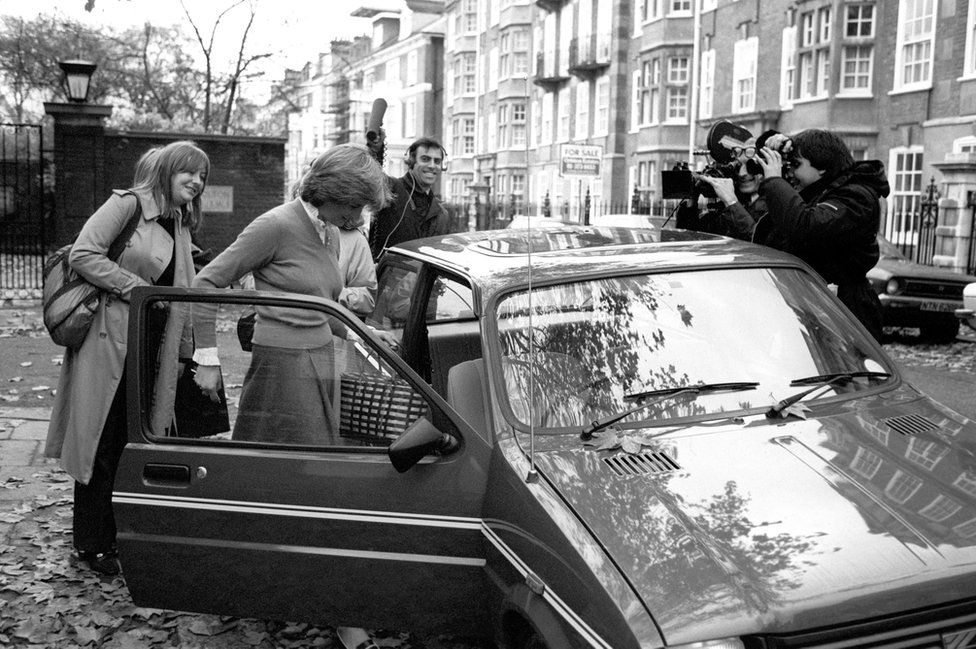 Lady Diana Spencer, surrounded by the media, leaving her Earl's Court flat to get into her car