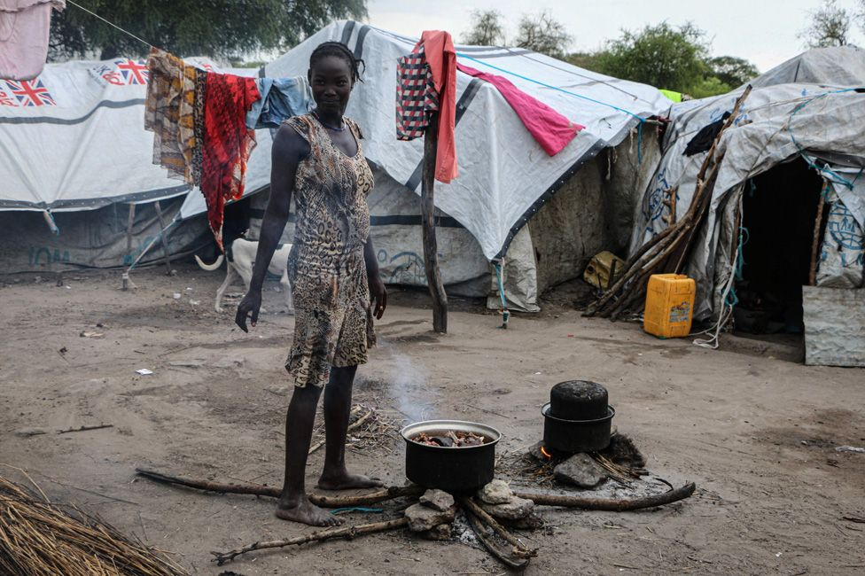 A South Sudanese woman cooks outside her shelter near a flooded area that has been isolated for about a month and a half due to the heavy rain in Pibor Town