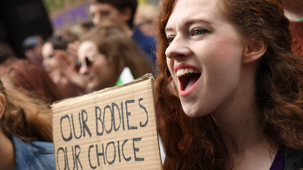 A woman, open mouthed, at a rally holds up a sign saying 'our bodies, our choice'