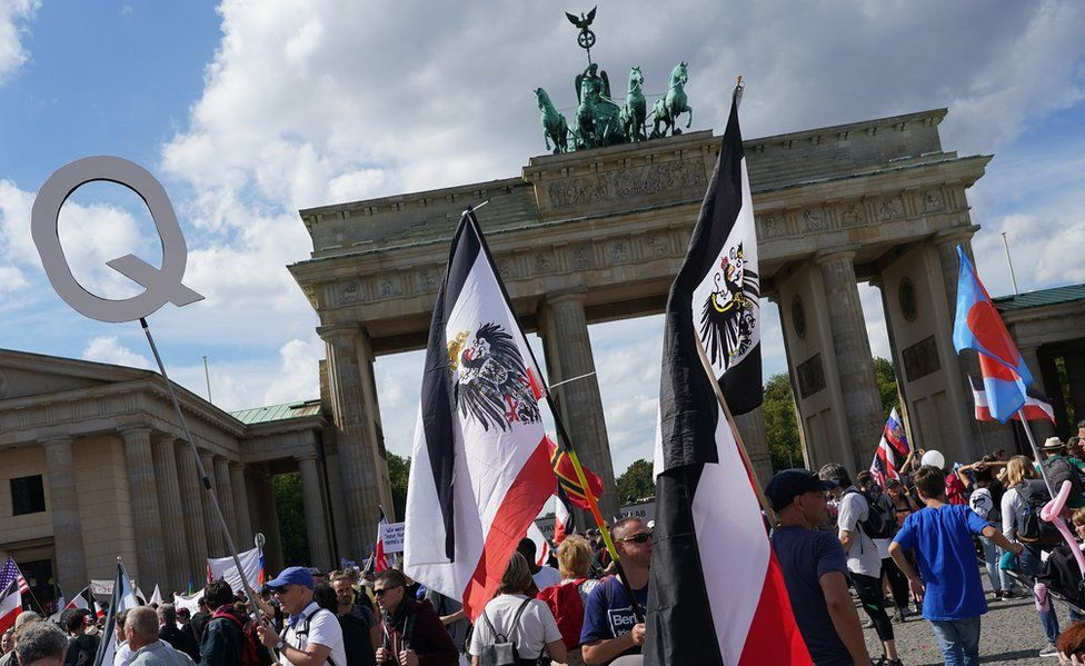 Men carry flags. including of the Kingdom of Prussia and the German Empire, at the Brandenburg Gate during protests against coronavirus-related restrictions and government policy on August 29, 2020 in Berlin, Germany