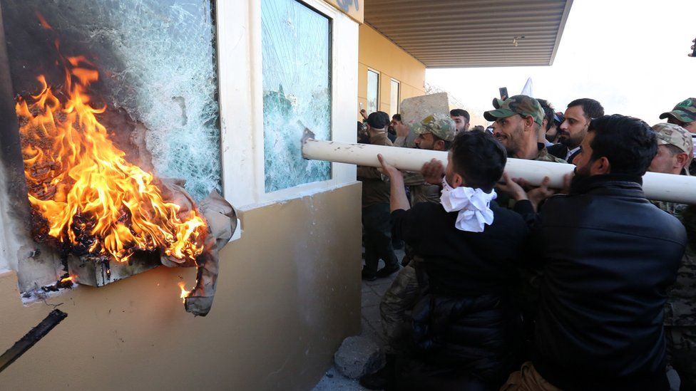 """Members of Iraqi Shia """"Popular Mobilisation Forces"""" armed group and their supporters attack the entrance of the US embassy in Baghdad, 31 December 2019"""