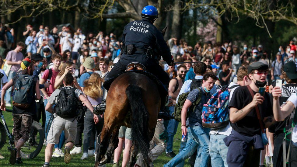 """Police on horses try to disperse people as they take part in fake festival called """"La Boum"""" organized by an anonymous group of people on Facebook for an April Fool""""s joke at the """"Bois de la Cambre, in Brussels, Belgium, 01 April 2021."""