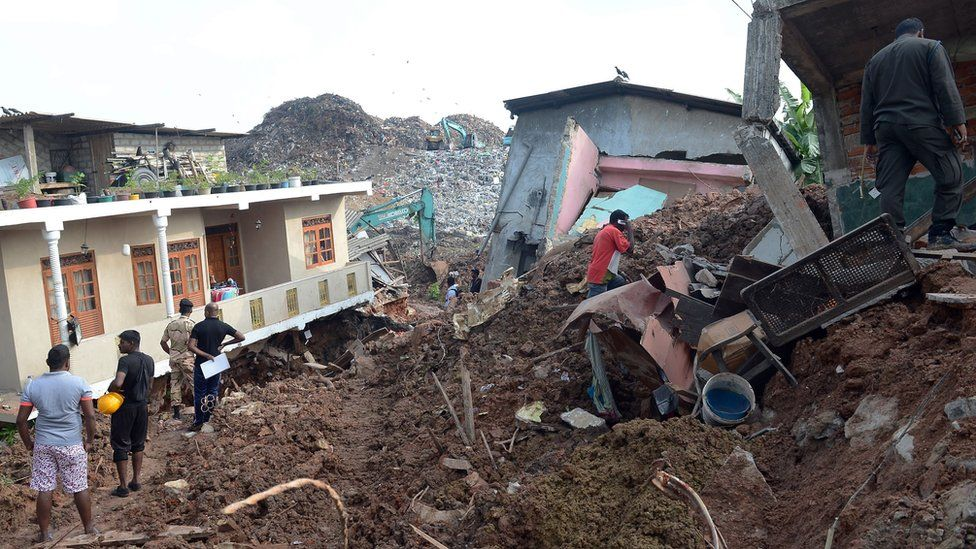 Sri Lankan residents walk through damaged homes at the site of a collapsed garbage dump in Colombo on April 15, 2017.