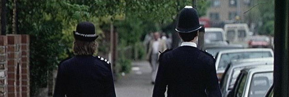 Two police officers walk down a road