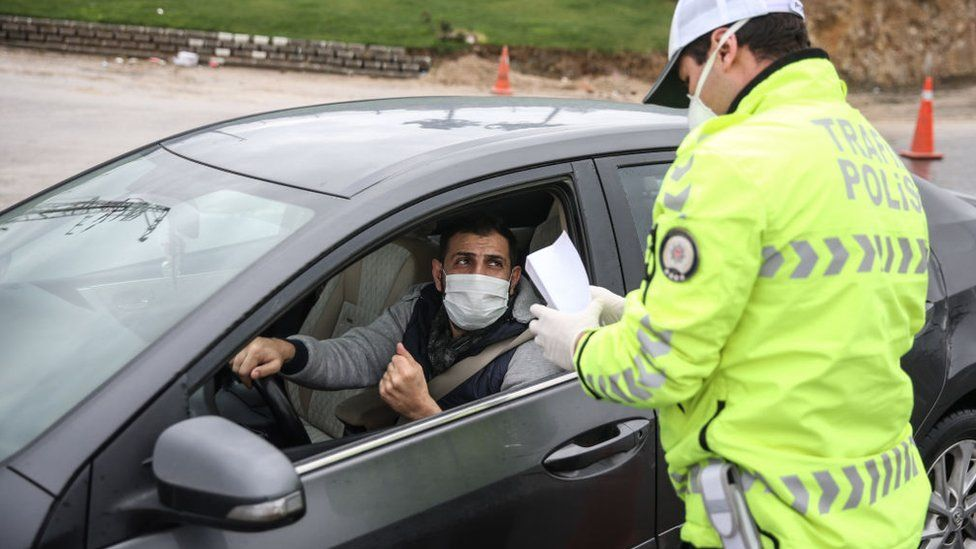A man wearing a face mask has paper checked by a police officer outside of his vehicle