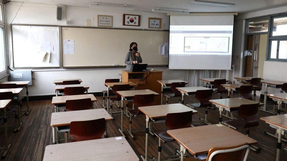 A teacher wears a mask as she gives a lesson on the first day of online class in an empty classroom