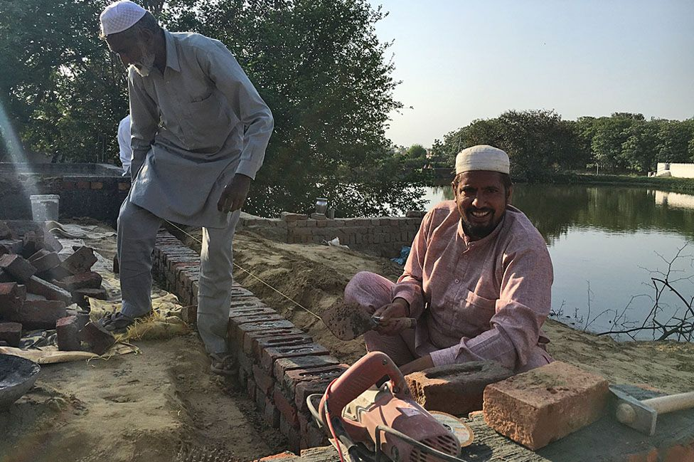 Raja Khan smiles as he works on the mosque