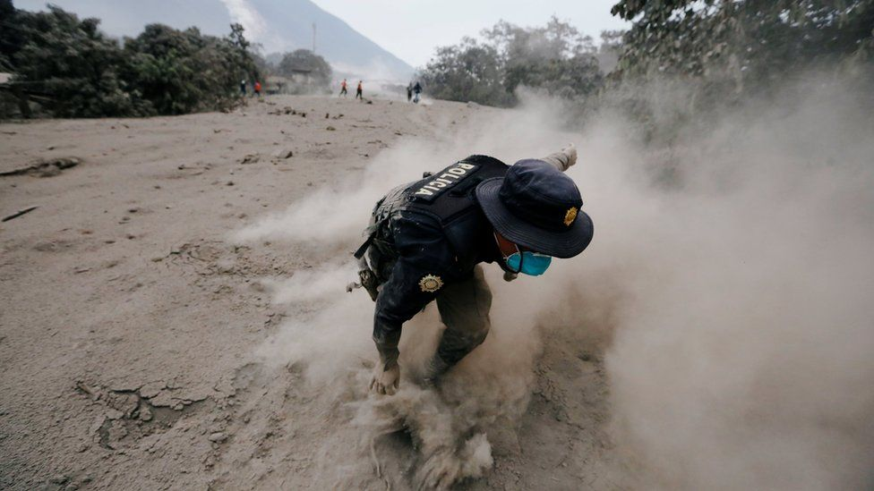 A police officer stumbles while running away after a the Fuego volcano spew new pyroclastic flow in the community of San Miguel Los Lotes in Escuintla, Guatemala, June 4, 2018