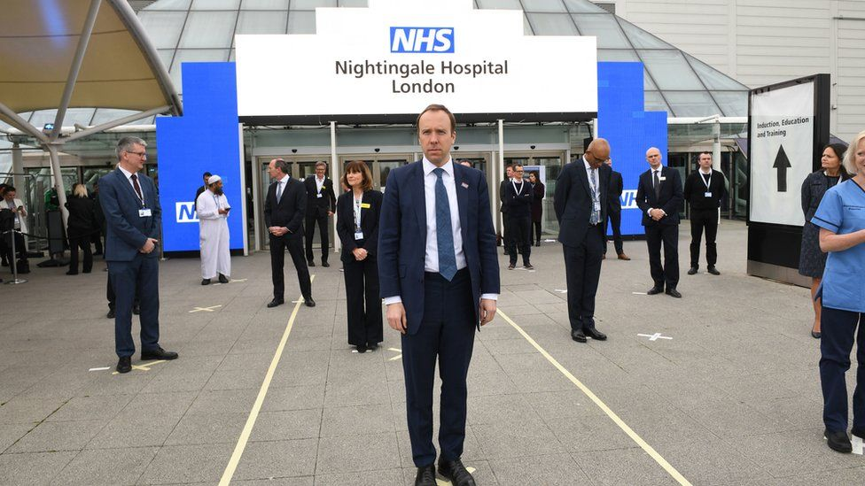 Health Secretary Matt Hancock and NHS staff stand on marks on the ground, put in place to ensure social distancing guidelines are adhered to, at the opening of the NHS Nightingale Hospital at the ExCel centre in London