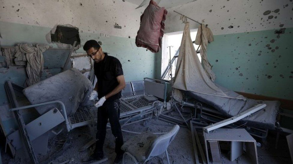 A Palestinian employee inspects damages at the al-Aqsa hospital in Deir al-Balah