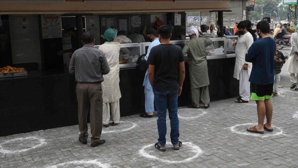 Customers wait to buy food in Lahore, Pakistan