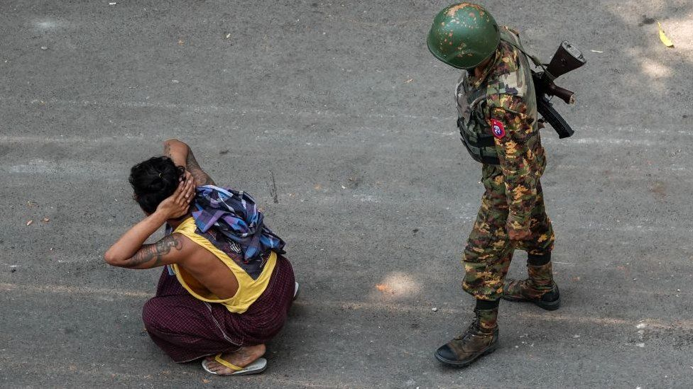 A soldier stands next to a detained man during a demonstration against the military coup in Mandalay on March 3, 2021